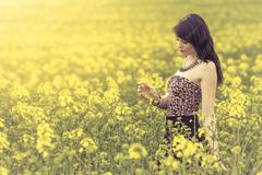 Beautiful woman in meadow of yellow flowers recognizing flower - stock photo