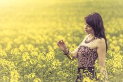 Beautiful woman in meadow of yellow flowers looking at flower Stock Photos