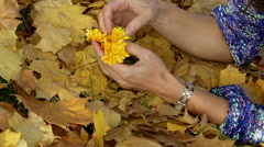 Woman playing with flower on the ground full of leaves Stock Footage