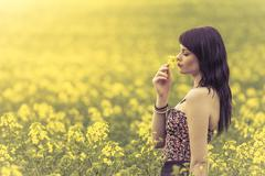 Beautiful woman in meadow of yellow flowers sniffing flower - stock photo