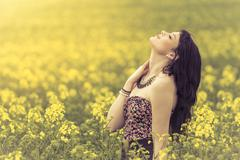 Beautiful woman in meadow of yellow flowers with face up - stock photo