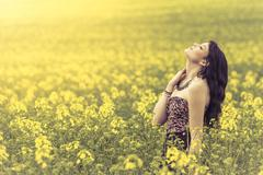 Beautiful woman in meadow of yellow flowers with head up - stock photo