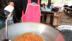 Women mixes nuts in cooking oil in Tak, Thailand. Stock Footage