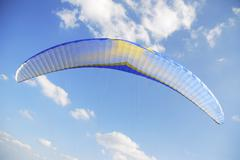 Paraglider with blue sky and clouds - stock photo