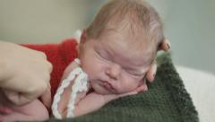 Female hands carefully arrange sleeping baby ready for shooting. Close up - stock footage