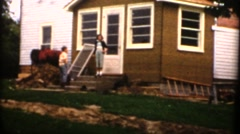 Vintage ,Granddaughter climbs up on stack of shingles Stock Footage