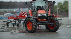 A tractor is parked outside in the parking lot Stock Footage