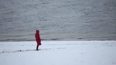 A girl walks along the riverbank in winter Stock Footage