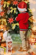 Stock Photo of Little child decorating with toys Christmas tree. Vertical color photo