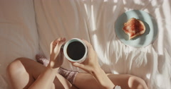 Overhead of woman in bed drinking coffee eating toast Stock Footage