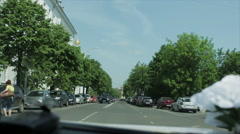 Driving through the city, green trees - stock footage