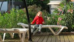 Little girl resting on a deck chair on the veranda of the house Stock Footage