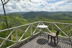 Chair and table on wooden deck over beautiful forest - stock photo