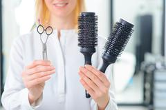 Professional stylist showing various tools - stock photo