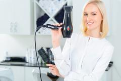 Stylist with hairdryer and brush Stock Photos