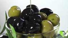 On olives in a bowl pouring olive oil. Slow motion 240 fps. Stock Footage