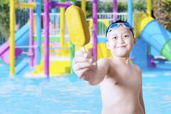Kid showing ice cream on the pool Stock Photos