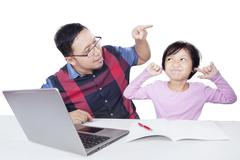Little girl closing her ears when scolded by her dad Stock Photos