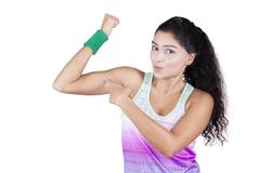 Woman pointing at her bicep - stock photo