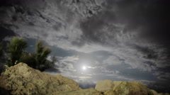 Night and the Moon above the clouds, rocks and underbrush Stock Footage