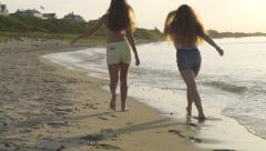 Fun Teenage Girls Twirl, Walk, Skip Down Beach, Away From Camera - stock footage