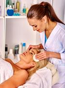 Woman middle-aged take face cleaning in spa salon - stock photo
