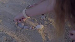 Stock Video Footage of Teens Make A Heart With Shells, Then Draw An Outline, On Beach