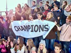 Sport fans holding champion banner on tribunes - stock photo