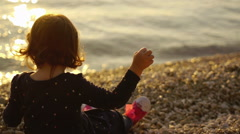 Small girl on the beach throwing stones into the sea - stock footage