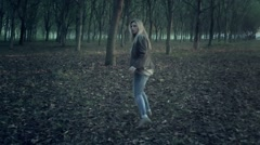 Scared afraid  woman running through park full of trees Arkistovideo