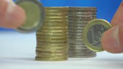 1€ 2€, one & two euro coins on the edge & stacks + fingers - focus change Stock Footage
