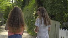 Teen Girls Walk Down Sunny Lane, With Beautiful Greenery, On A Sunny Summer Day Stock Footage