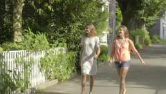 Two Teenage Girls Walk Down Middle Of Road In Beautiful Neighborhood Stock Footage