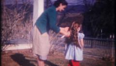 2860 - mom combs out the braids in daughters hair - vintage film home movie - stock footage