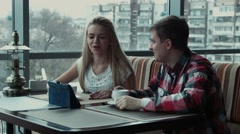 The guy shows something on the touchpad to the girl in cafe Stock Footage