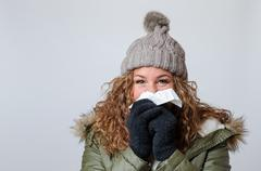 Young woman with a cold blowing her nose Stock Photos