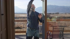 A man cleaning the large house windows during the day - stock footage