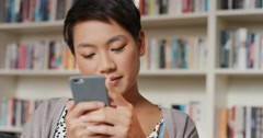 Beautiful Asian woman at home using internet on smart phone sending messages - stock footage