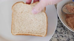 A man puts tuna fish on bread for a sandwich Stock Footage