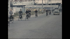 Vintage 16mm film, 1960, France, shipyard workers going home on bikes Stock Footage