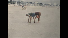 Vintage 16mm film, 1960, France, people on the beach picking shells Stock Footage