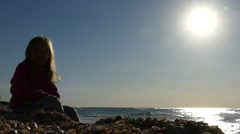 Girl playing with seashells on the shore of the Mediterranean Stock Footage