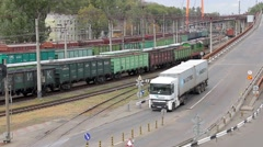 Container truck driving on the road and cargo train moves on railway. - stock footage