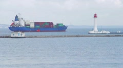 Cargo ship sailing  past the lighthouse to open sea Stock Footage