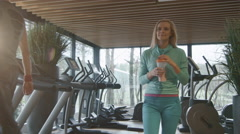 Attractive blond caucasian girl is drinking a protein shake drink in gym Stock Footage