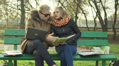 Boy trying to explain something to his irritated girlfriend in the park Stock Footage