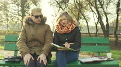 Morose students sitting on the bench in the park and talking Stock Footage