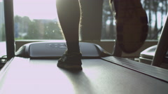 Close-up footage of male silhouette against sun running on treadmill in gym Stock Footage