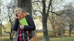 Happy girl standing in the park with notebook and chatting on cellphone Stock Footage