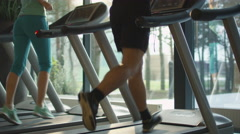 Young athletic men and women exercising and running on treadmill in sport gym - stock footage